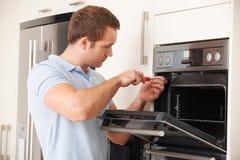 Mens die Binnenlands Oven In Kitchen herstellen royalty-vrije stock afbeeldingen