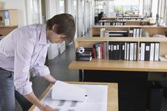 Mens die Blauwdruk in Bureau bestuderen Stock Foto