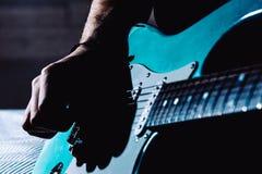 Mens die blauwe elektrische gitaar spelen dicht omhoog thuis Het praktizeren gitaar stock afbeeldingen