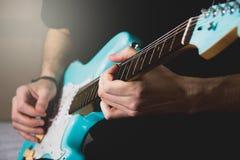 Mens die blauwe elektrische gitaar spelen dicht omhoog thuis Het praktizeren gitaar royalty-vrije stock afbeeldingen
