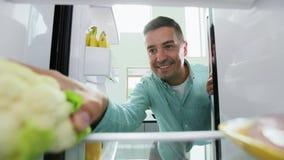 Mens die bloemkool van koelkast thuis keuken nemen stock videobeelden