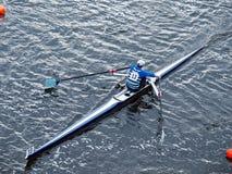 Mens die in boot op water roeit Stock Afbeeldingen