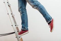 Mens die bovenop ladder het beklimmen bereiken stock fotografie
