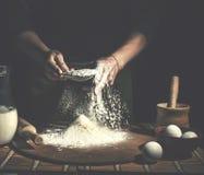 Mens die brooddeeg op houten lijst in een bakkerij dicht omhoog voorbereiden Voorbereiding van Pasen-brood stock afbeelding