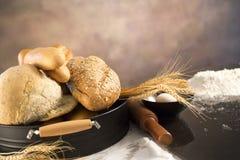 Mens die broodjes voorbereiden bij lijst in bakkerij stock afbeeldingen