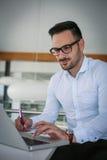 Mens die in bureau aan laptop en het schrijven document werken Royalty-vrije Stock Foto