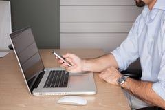 Mens die in bureau telefoon controleert tijdens vergadering. royalty-vrije stock afbeeldingen