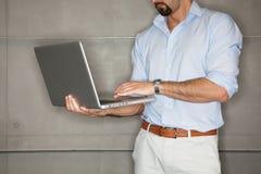 Mens die in bureau zijn presentatie controleert op laptop. royalty-vrije stock fotografie