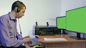 Mens die in call centresteun werken voor computer met hoofdtelefoons en microfoon stock video