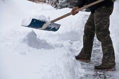 Mens die in camobroek sneeuw ontruimen bij zijn huis royalty-vrije stock fotografie