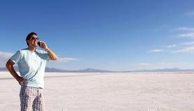 Mens die cellphone in de woestijn gebruiken Stock Foto's