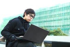 Mens die computer met behulp van openlucht Stock Foto's
