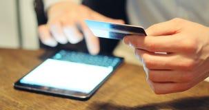 Mens die computer voor online aankoop met creditcard met behulp van stock video