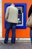 Mens die contant geldmachine, ATM, cashpoint, of bankmachine met behulp van stock afbeelding