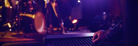 Mens die correcte mixer met uitvoerders op verlicht stadium in nachtclub in werking stellen stock afbeelding