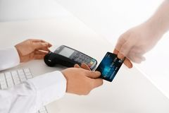 Mens die creditcard geven aan teller bij het venster van de contant geldafdeling stock afbeelding