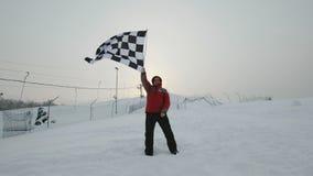 Mens die de afwerkingsvlag golven bij de winter stock footage