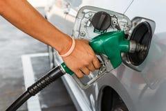 Mens die de auto met brandstof op een benzinestation opnieuw vullen Stock Foto's