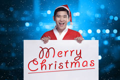 Mens die de banner van de het kostuumholding van de Kerstman met het vrolijke Kerstmis schrijven dragen Royalty-vrije Stock Foto