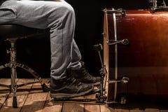 Mens die de bastrommel, houten Raad met een zwarte achtergrond spelen Stock Foto