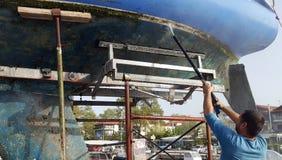Mens die de bodem van een zeilboot schoonmaken stock afbeeldingen