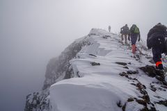 Mens die de bovenkant van berg stormen stock afbeelding
