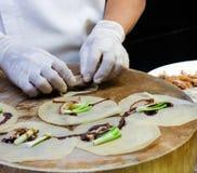 Mens die de broodjes van de Rijstomslag in straatmarkt maken stock foto's