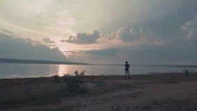 Mens die de fluit spelen bij zonsondergang stock footage