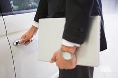 Mens die de handvatten van een autodeur met laptop houden Royalty-vrije Stock Afbeelding