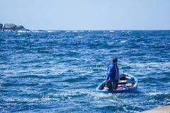 Mens die de haven voor visserij verlaten Stock Foto's