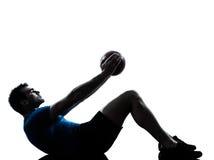 Mens die de houding van de de geschiktheidsbal van de trainingholding uitoefenen Stock Afbeeldingen