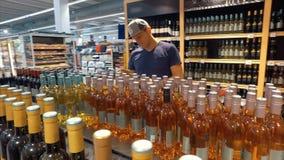 Mens die de juiste wijn in een supermarkt kiezen stock footage
