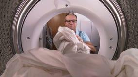Mens die de kleren laden aan wasmachine stock videobeelden