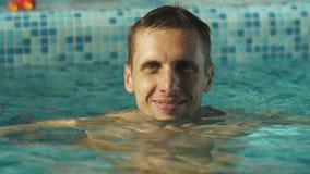 Mens die in de pool glimlachen stock video