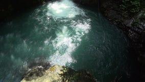 Mens die in de rivier met waterval langzame mo springen stock video