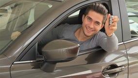 Mens die de sleutel van zijn nieuwe auto tonen stock videobeelden