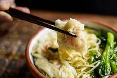 Mens die de soep van de garnalen wonton noedel met choy som eten Stock Fotografie