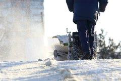 Mens die de straat van speciale sneeuw handtractor schoonmaken royalty-vrije stock fotografie
