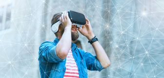 Mens die in de straat in vergrote werkelijkheidshoofdtelefoon lopen Virtuele werkelijkheid en futuristisch technologieconcept stock foto