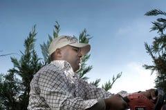 Mens die in de tuin werken die de bomen snijden Stock Foto