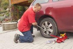 Mens die de vernietigde band op zijn auto veranderen die de noten met een wielmoersleutel losmaken vóór het opkrikken van het voe stock foto