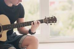 Mens die in denimborrels met aan het venster met zijn gitaarmuziek zitten, musicus, hobby, levensstijl, hobby Royalty-vrije Stock Afbeelding