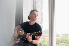 Mens die in denimborrels met aan het venster met zijn gitaarmuziek zitten, musicus, hobby, levensstijl, hobby Stock Afbeelding