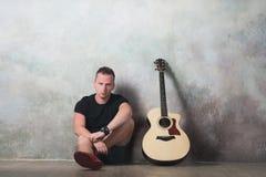 Mens die in denimborrels naast een gitaar op de muurachtergrond zitten in stijl grunge, muziek, musicus, hobby, levensstijl, hobb Stock Foto's