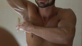 Mens die deodorant op oksel in badkamers, huidzorg en dagelijkse hygiëne toepassen stock footage