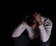 Mens die depressie op donkere achtergrond tonen Stock Foto's