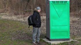 Mens die dichtbij groen draagbaar toilet in het park wachten stock footage