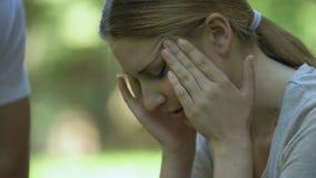Mens die dichtbij meisje blijven die sterke hoofdpijn, vriendelijke niet onverschillige voorbijganger voelen stock footage