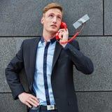 Mens die die vraag met telefoon maken aan muur wordt vastgebonden Royalty-vrije Stock Fotografie