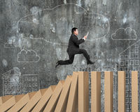 Mens die digitale tablet gebruiken die op dalende houten domino's lopen Royalty-vrije Stock Afbeelding